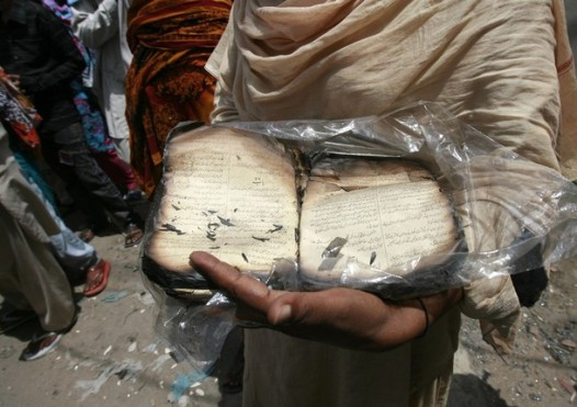 A Christian woman shows a charred Bible, written in Urdu, to the photographer outside her torched house in Gojra town located in Punjab province August 4, 2009. Islamist militants from groups linked to al Qaeda and the Taliban are suspected of being behind the mob violence that killed eight Christians in central Pakistan over the weekend, a senior government official said on Tuesday.  REUTERS/Mohsin Raza     (PAKISTAN RELIGION POLITICS CRIME LAW)
