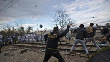 Migrants hurl stones at Macedonian policemen during clashes at the Greek-Macedonian border, near the northern Greek village of Idomeni, on Saturday, Nov. 28, 2015. Tension has flared on the Greek side of the Greece-Macedonia border when a migrant who was stopped from crossing into Macedonia, suffered severe burns when he climbed on top of a stationary train carriage and touched a overhead power cable.(AP Photo/Muhammed Muheisen)