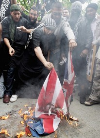 LONDON, ENGLAND - SEPTEMBER 11: Muslim protesters burn an American flag outside the American Embassy, in Grosvenor Square, on September 11, 2010 in London, England. Controversial US pastor, Terry Jones has sparked protests across the world after planning to stage an International Burn a Koran Day on 9/11, the anniversary of the 2001 attacks on the World Trade Centre in New York. Mr Jones has since postponed the event after sparking international condemnation and protests around the world. (Photo by Dan Kitwood/Getty Images)