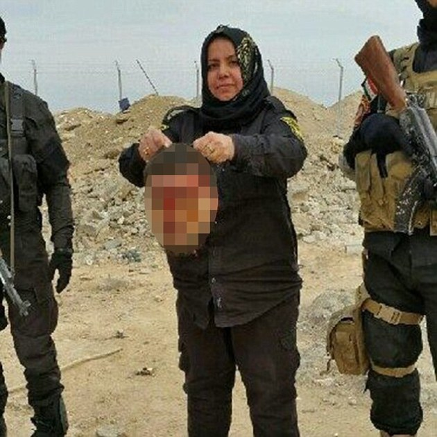 Wahida Mohamed Al-Jumaily holds up what appears to be the severed head of an enemy.