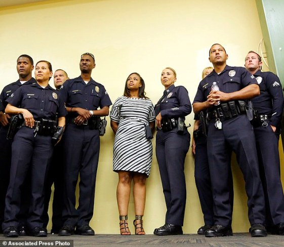 Rodney King's daughter Lora King, 32, stands shoulder-to-shoulder with a group of Los Angeles Police Officers as they meet with a group of young people who have had their own run-ins with police at a meeting of the Los Angeles Conservation Corps, which provides at-risk youth with job training, education and work, in downtown Los Angeles Thursday, Sept. 15, 2016. She was just 7 when her father was beaten by the LAPD. Her message: It's more important to build bridges with officers than to stand against the, and that a whole police department can't be judged by the actions of a few.(AP Photo/Reed Saxon)
