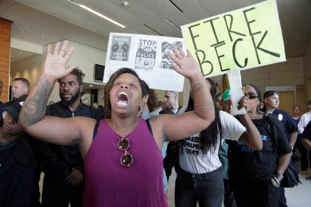 Protesters demand the firing of Los Angeles Police Chief Charlie Beck over a police-involved shooting of a black man over the weekend during a news conference at LAPD headquarters on Monday, Oct. 3, 2016. The chief disclosed details of Saturday's shooting of Carnell Snell, in South Los Angeles and a separate fatal police shooting of a Hispanic man Sunday amid heightened tensions over police shootings involving blacks and other minorities in California and elsewhere. (AP Photo/Nick Ut)